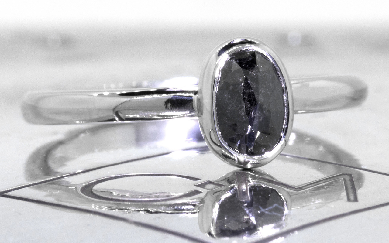 .57 carat  oval, rose cut natural black bezel set diamond ring set in 14k white gold 1/2 round band. 3/4 view on metal background with Chinchar/Maloney logo