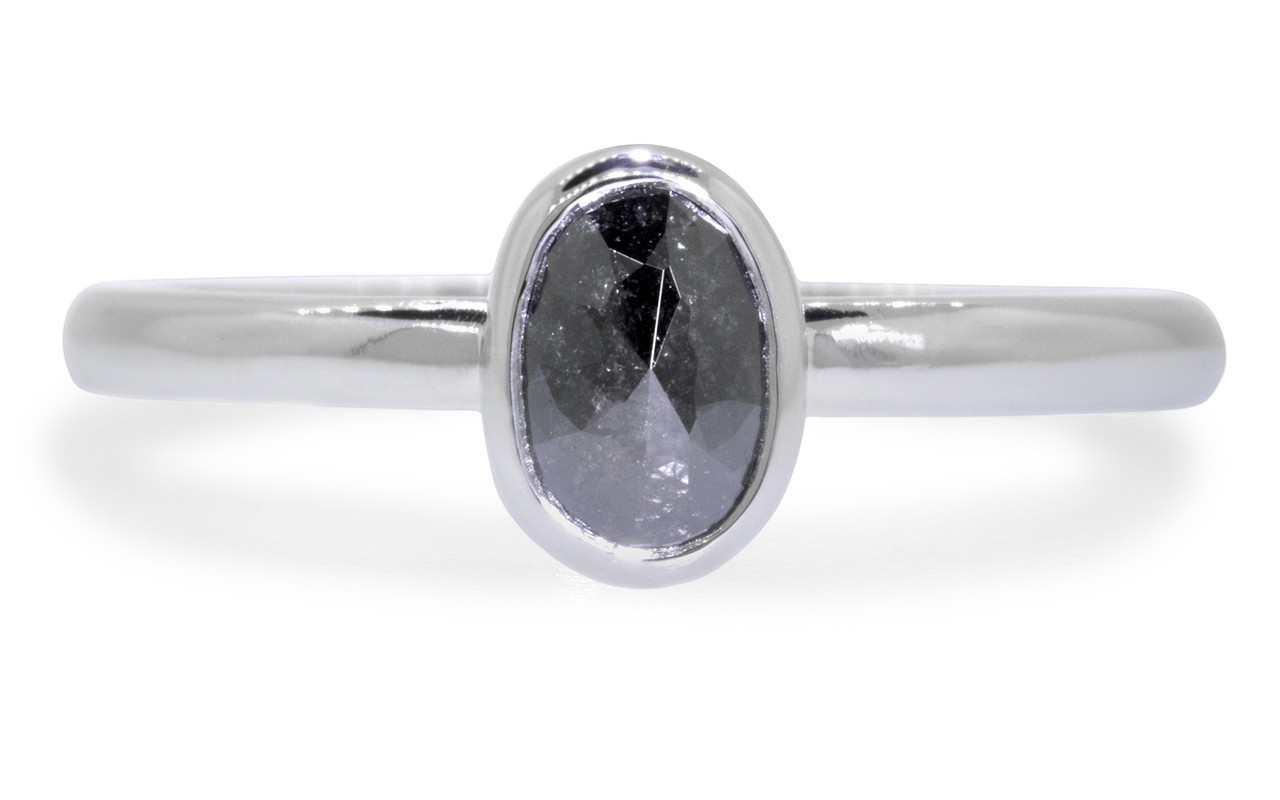 .57 carat  oval, rose cut natural black bezel set diamond ring set in 14k white gold 1/2 round band. Front view on white background