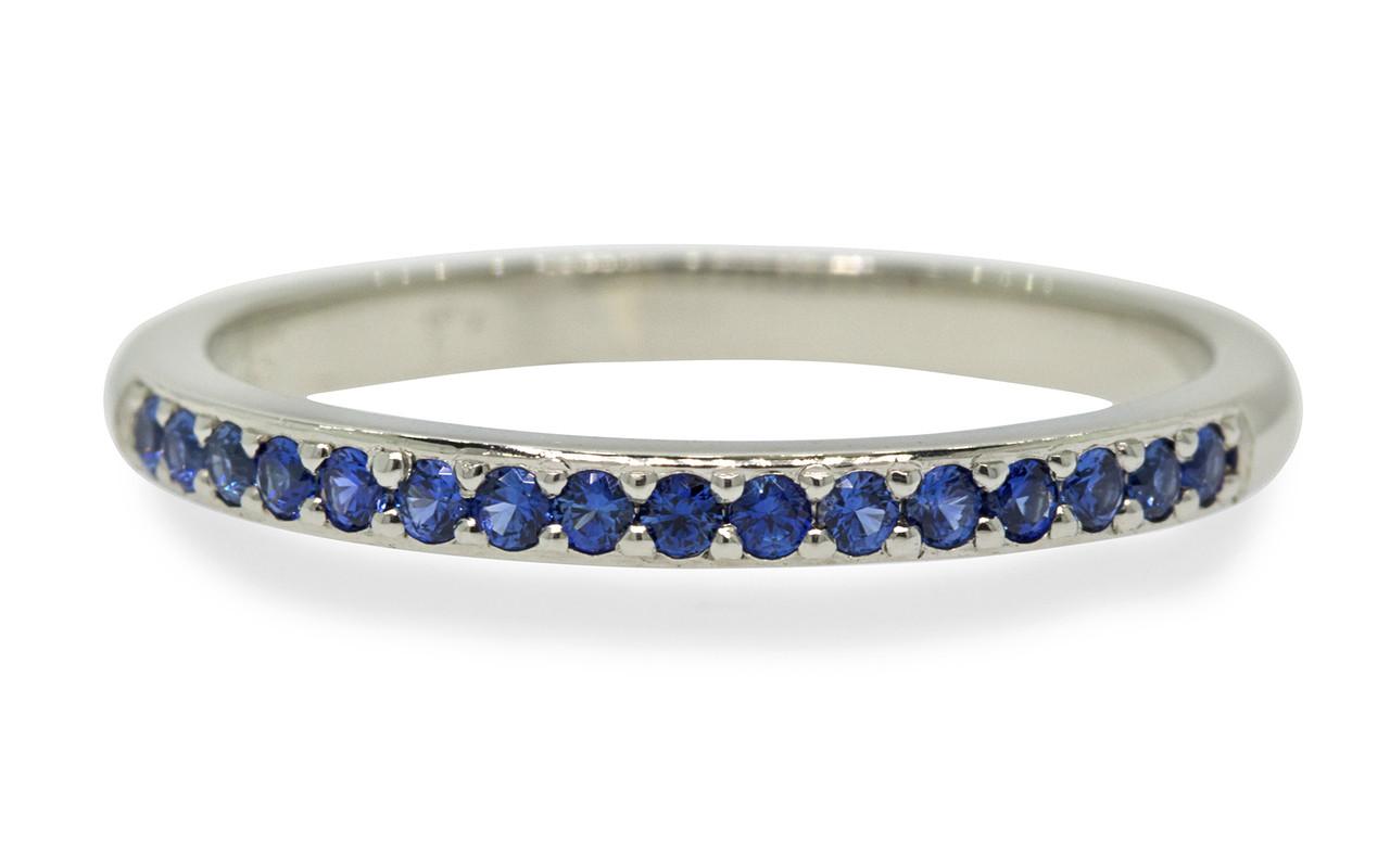 14k white gold wedding band with 16 brilliant cut blue sapphires half way around band on white background