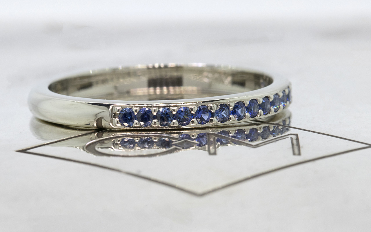 14k white gold wedding band with 16 brilliant cut blue sapphires half way around band on metal background with Chinchar/Maloney logo. side view