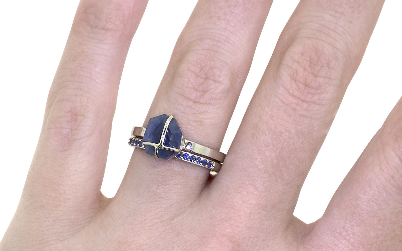 14k white gold wedding band with 16 brilliant cut blue sapphires half way around modeled on hand with blue sapphire ring.