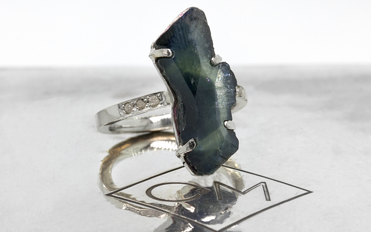 5.93 carat hand-cut blue green sapphire six 1.2mm rough diamonds set in 14k white gold band 3/4 view on metal background with Chinchar/Maloney logo