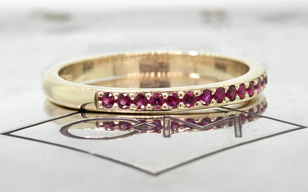 14k yellow gold wedding band with 16 brilliant rubies set half way around band on metal background with Chinchar/Maloney logo side view