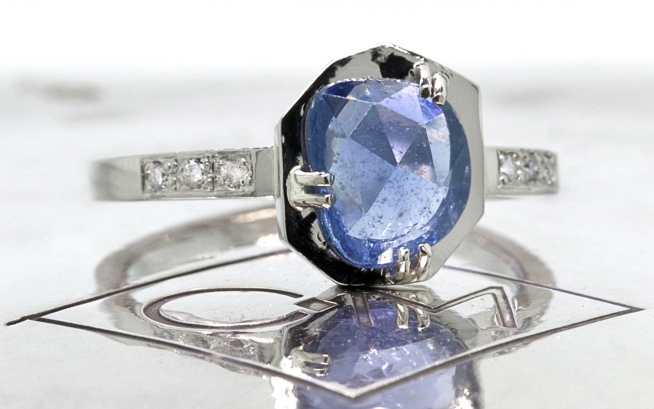 KIKAI 1.37 carat free form rose cut blue sapphire with six 1.2mm brilliant white diamonds set in band set in 14k white gold flat band. 3/4 view on metal background with Chinchar/Maloney logo Part of our New Classic Collection