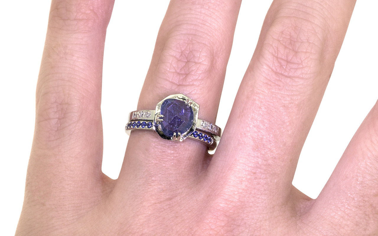 KIKAI 1.37 carat free form rose cut blue sapphire with six 1.2mm brilliant white diamonds set in band set in 14k white gold flat band. With wedding band with 16 blue sapphires set in 14k white gold on a hand Part of our New Classic Collection