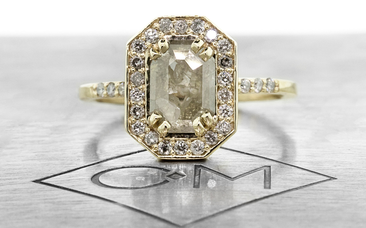 KATLA New Classic .60 carat fancy cut gray diamond prong set in octangualr  14k yellow gold setting with brilliant, gray diamonds surround the center diamond in a halo as well as each corner of the setting and each shoulder of the ring. shown on metal background with Chinchar/Maloney logo.