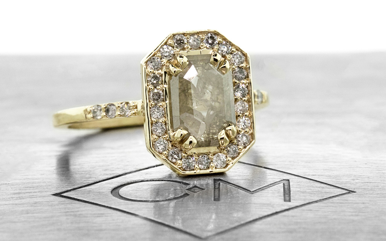 KATLA New Classic .60 carat fancy cut gray diamond prong set in octangualr  14k yellow gold setting with brilliant, gray diamonds surround the center diamond in a halo as well as each corner of the setting and each shoulder of the ring. shown on metal background with Chinchar/Maloney logo.3/4 view