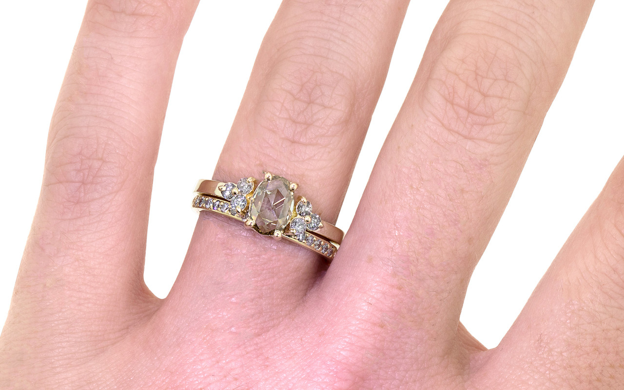 .79 carat oval, rose-cut prong set champagne diamond ring with six 2mm brilliant gray diamond clusters on either side of main setting set in 14k yellow gold flat band. With Wedding Band with 16 brilliant gray diamonds set in 14k yellow gold on a hand