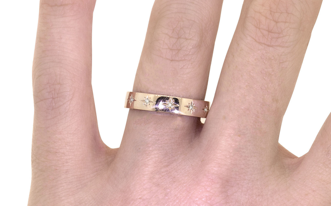 14k rose gold wedding band with brilliant white pave diamonds in star detail modeled on hand