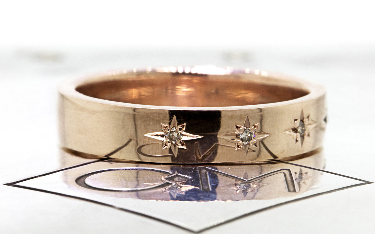 14k yellow gold wedding band with brilliant champagne diamonds set in star detail half way around band. Side view on metal back ground with Chinchar/Maloney logo