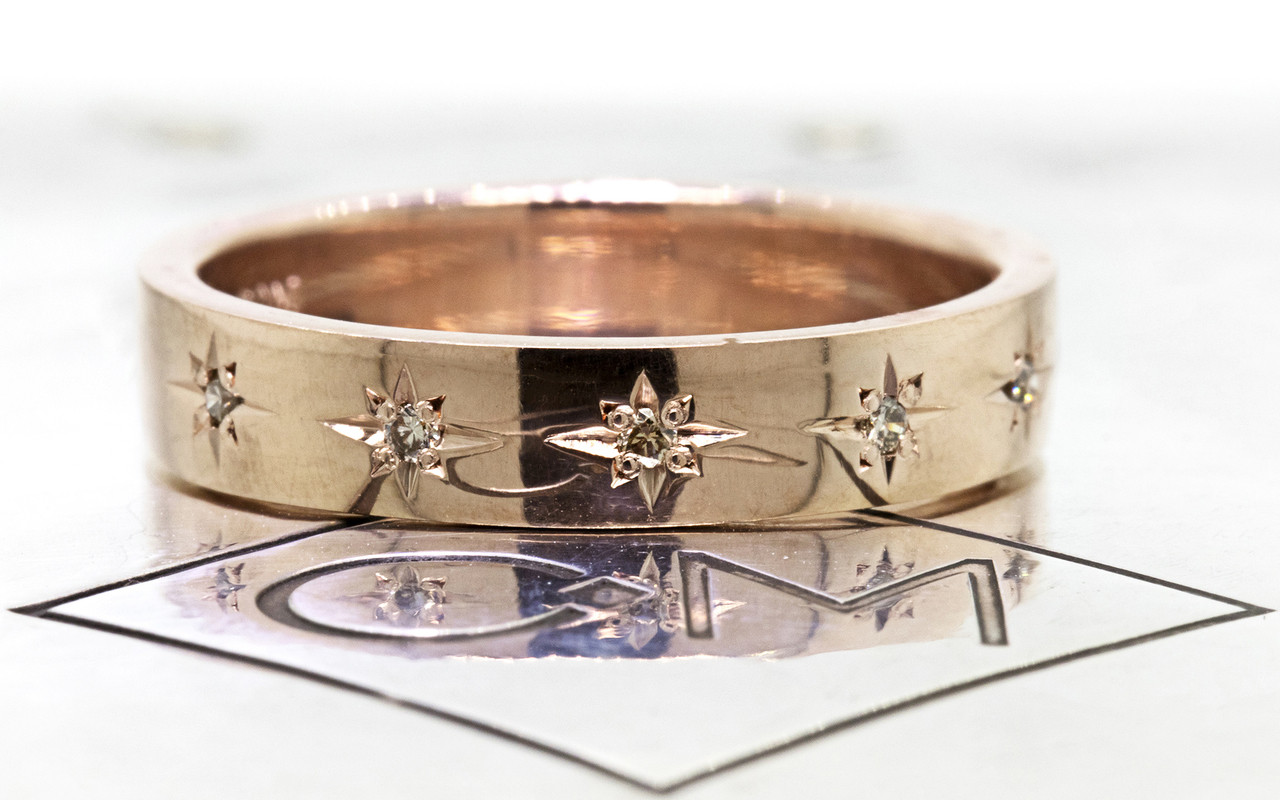 14k yellow gold wedding band with brilliant champagne diamonds set in star detail half way around band on metal back ground with Chinchar/Maloney logo