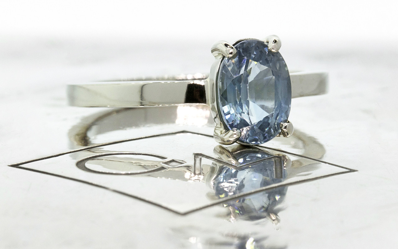 1.59 carat oval rose cut blue sapphire set in 14k white gold flat band. 3/4 on metal background with Chinchar/Maloney logo