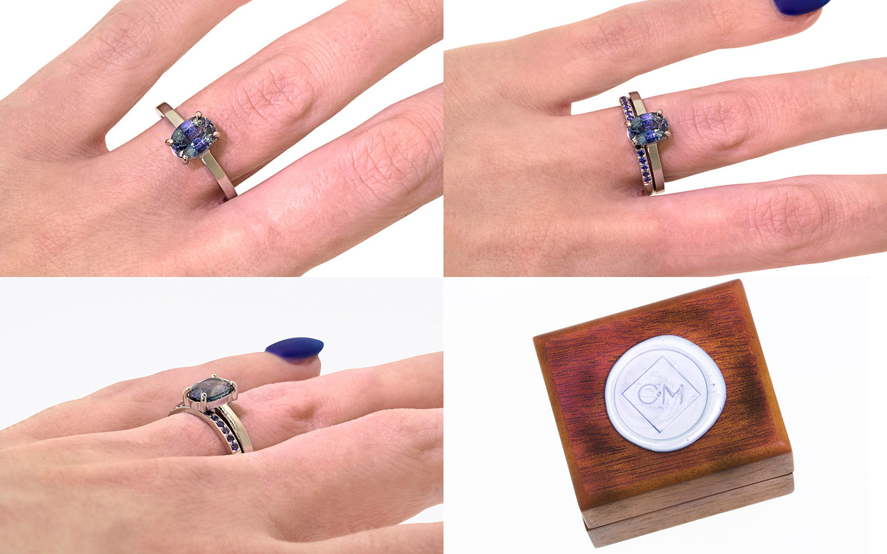 1.59 carat oval rose cut blue sapphire set in 14k white gold flat band. With Wedding band with 16 blue sapphires set in 14k white gold on a hand with wooden box stamped with wax seal Chinchar/Maloney logo