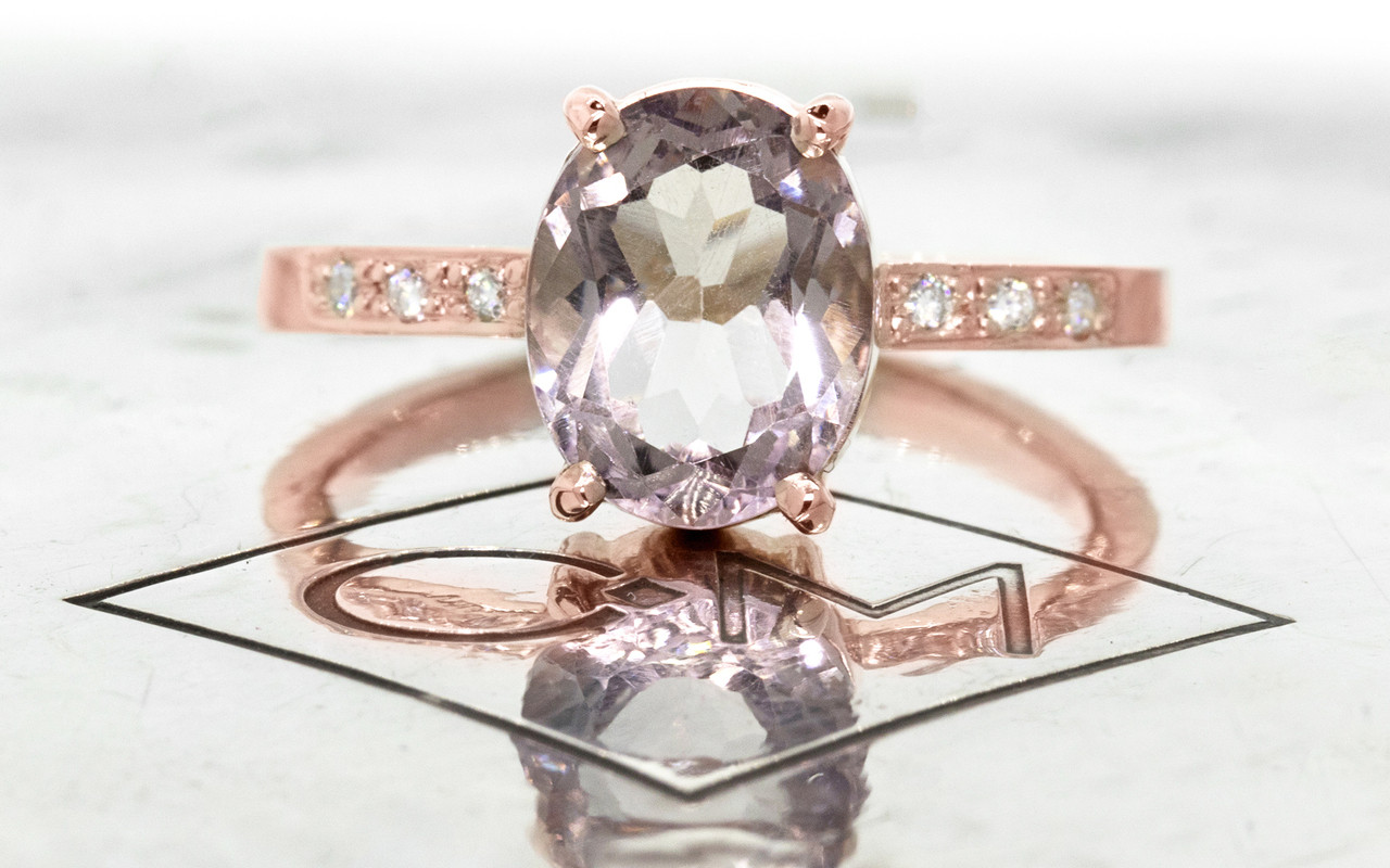 1.99 carat oval faceted cut light pink morganite with six 1.2mm brilliant white diamonds in band set in 14k rose gold flat band. Front view on metal background with Chinchar/Maloney logo