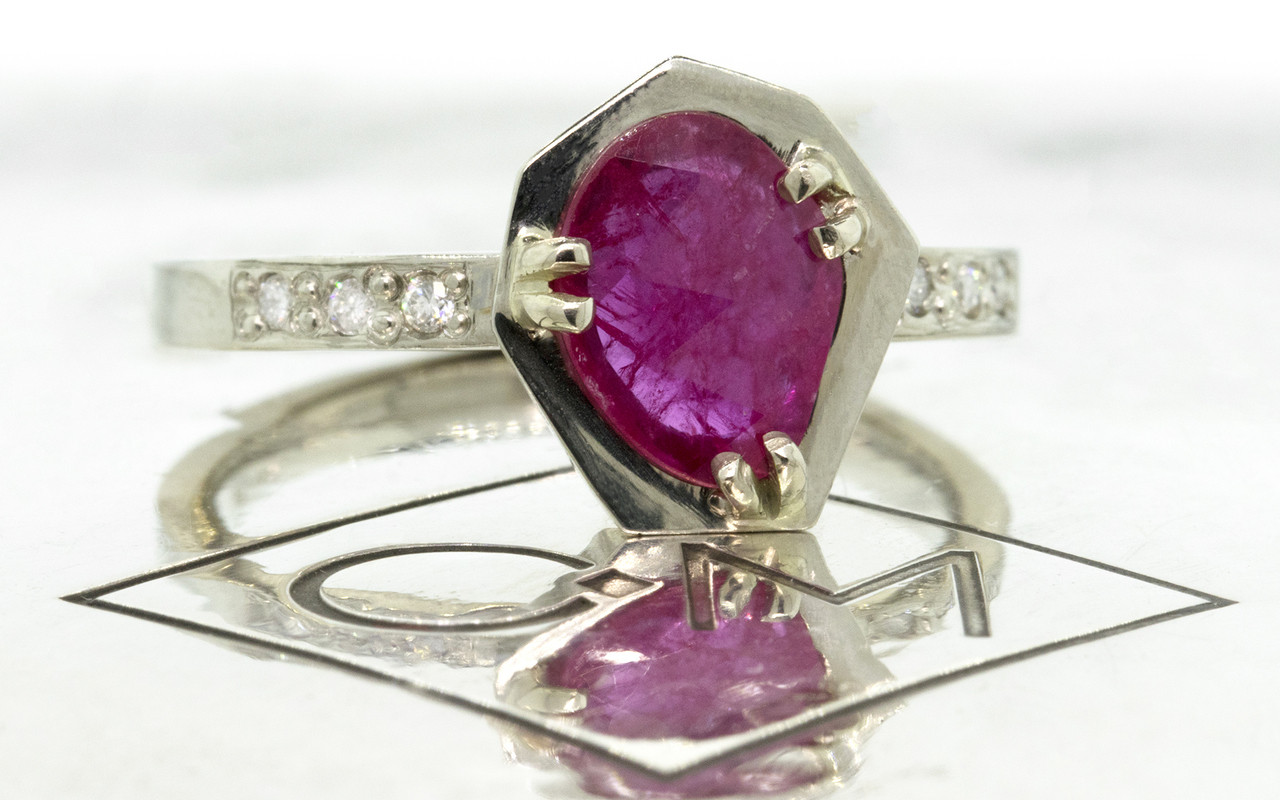 KIKAI .84 carat ruby in 14k white gold six 1.2mm brilliant white diamonds set in band 3/4 view on metal background with Chinchar/Maloney logo from New Classic Collection