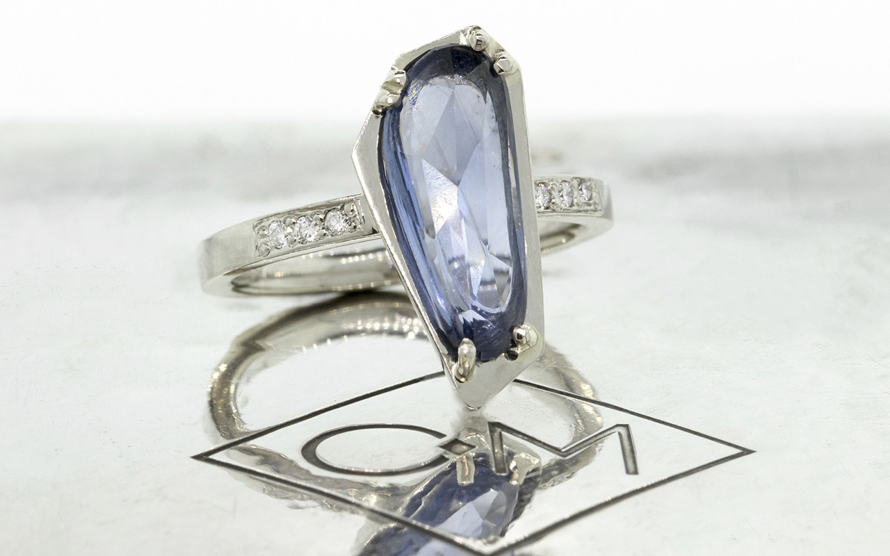 KIKAI 2.46 carat free-form, rose cut blue sapphire with 6 1.2mm brilliant white diamonds set in band set in 14k white gold flat band. Part of New Classic Collection. 3/4 view on metal background with Chinchar/Maloney logo