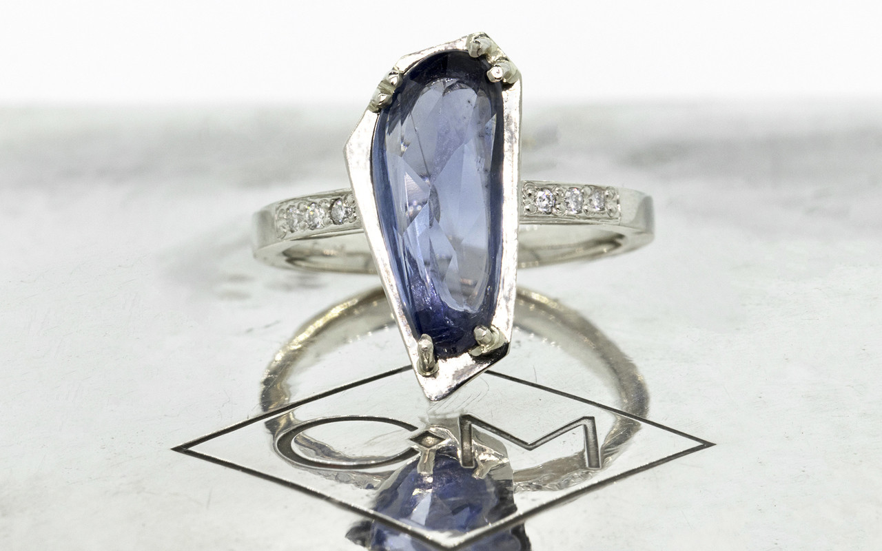 KIKAI 2.46 carat free-form, rose cut blue sapphire with 6 1.2mm brilliant white diamonds set in band set in 14k white gold flat band. Part of New Classic Collection. front view on metal background with Chinchar/Maloney logo