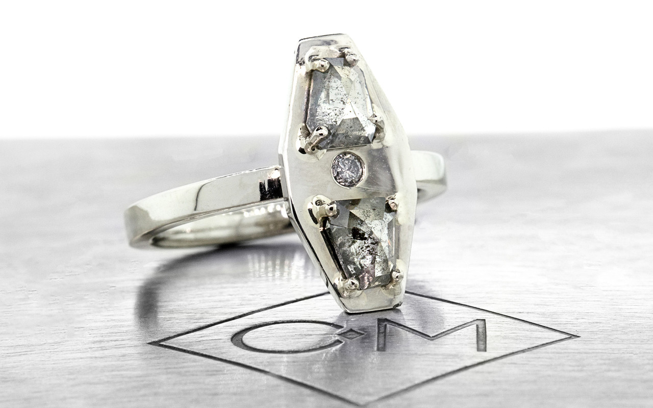 TOBA .73 carat fancy rose-cut translucent salt and pepper diamonds ring with one 2mm gray pave diamond set into main setting set in 14k white gold flat band. Part of our New Classic Collection. 3/4 view on metal background with Chinchar/Maloney logo