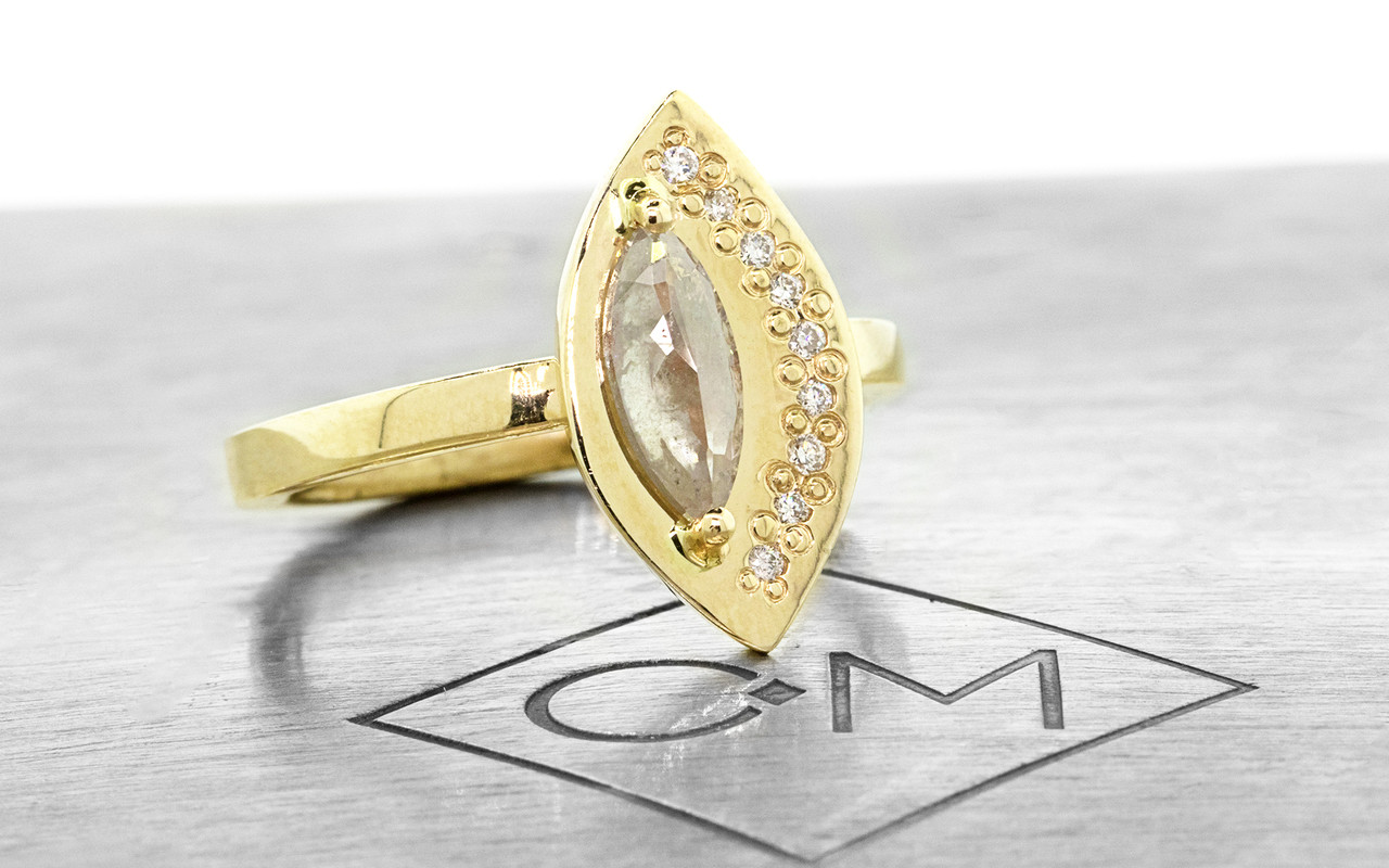 TOBA .54 carat marquise rose-cut glowing light gray diamond ring with nine 1mm brilliant white diamonds set along the edge of the main setting set in 14k yellow gold flat band. Part of our New Classic Collection. 3/4 view on metal background with Chinchar/Maloney logo