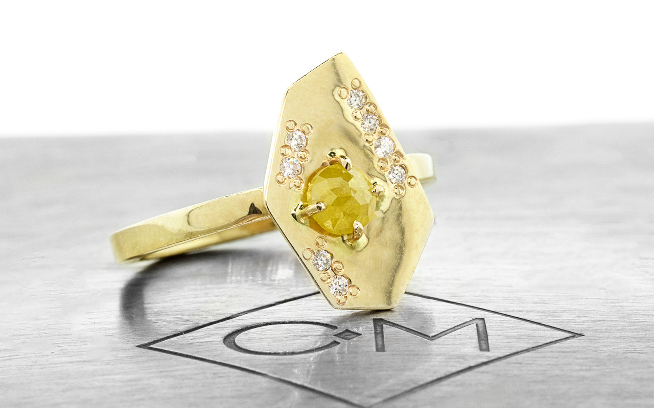 TOBA .33 carat rose-cut warm yellow diamond ring with eight 1mm brilliant white diamonds set into main setting on either side of main diamond set in 14k yellow gold flat band. Part of our New Classic Collection.  3/4 view on metal background with Chinchar/Maloney logo