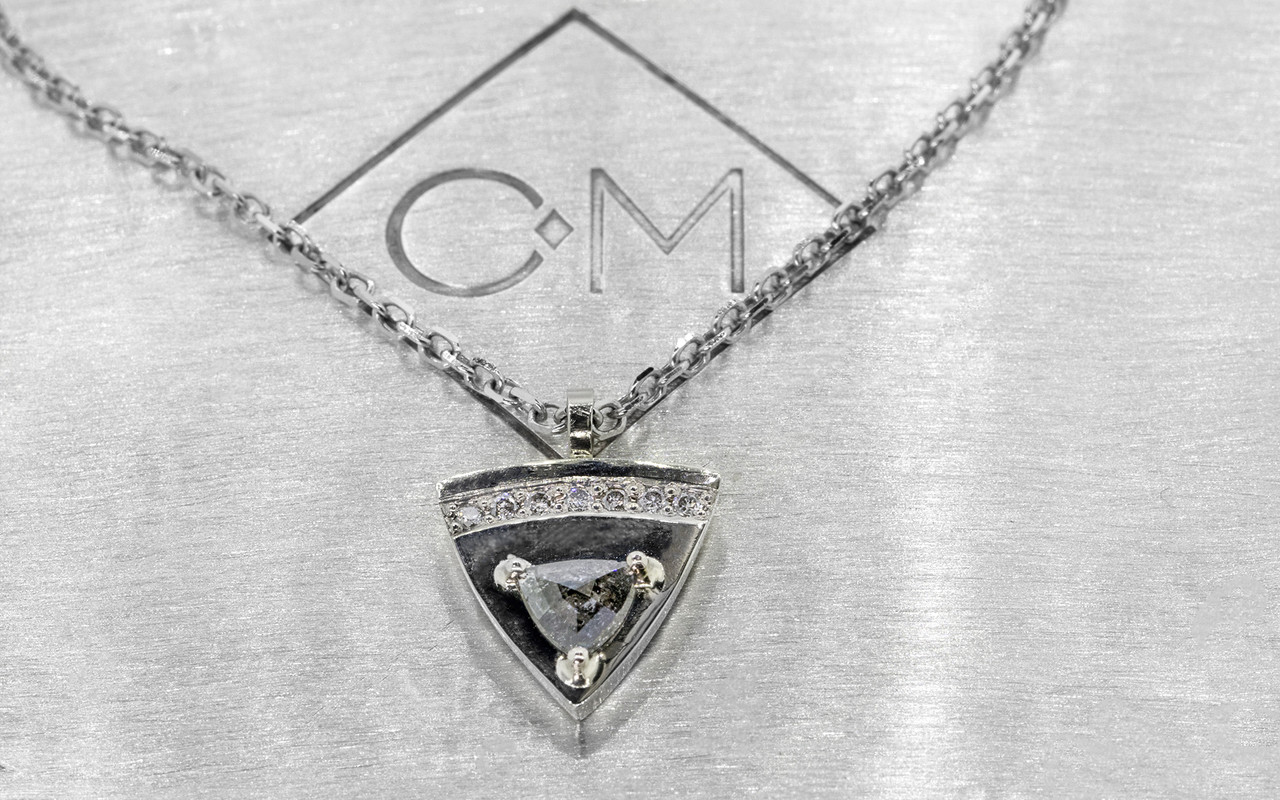 TOBA .18 carat triangle rose-cut salt and pepper diamond necklace with seven 1.25mm brilliant gray diamonds set across the top of the pendent set in 14k white gold with chain. Part of our New Classic Collection. Side view on metal background with Chinchar/Maloney logo