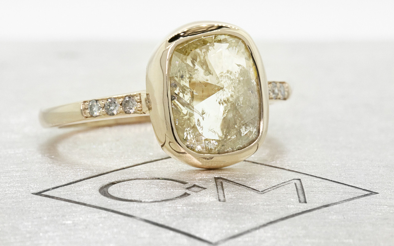 2.46 carat cushion, rose cut translucent rustic champagne/white bezel set diamond ring set in 14k yellow gold with six 1.2mm brilliant gray diamonds set in 1/2 round band. 3/4 view on metal background with Chinchar/Maloney logo