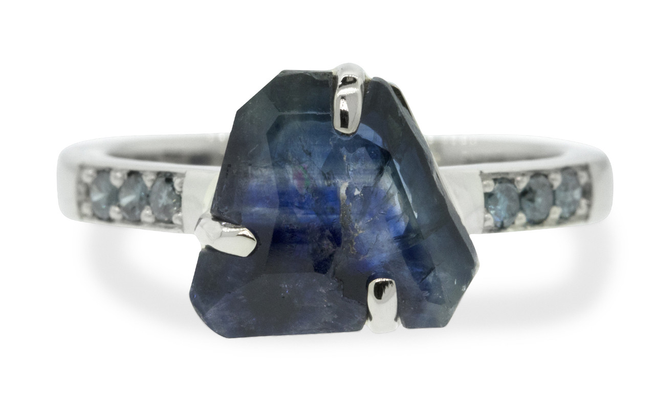 2.45 carat hand-cut deep blue signature inlaid prong set  sapphire and blue diamond ring in 14k white gold. With six 1.7mm brilliant blue diamonds bead-set in 1/2 round 14k recycled white gold band. Part of our Refined Rough Collection. Front view on white background.