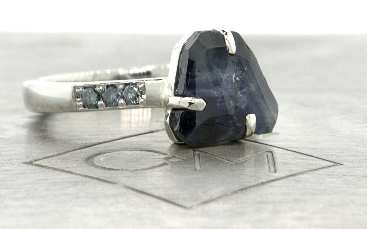 2.45 carat hand-cut deep blue signature inlaid prong set  sapphire and blue diamond ring in 14k white gold. With six 1.7mm brilliant blue diamonds bead-set in 1/2 round 14k recycled white gold band. Part of our Refined Rough Collection. 3/4 view on metal background with Chinchar/Maloney logo