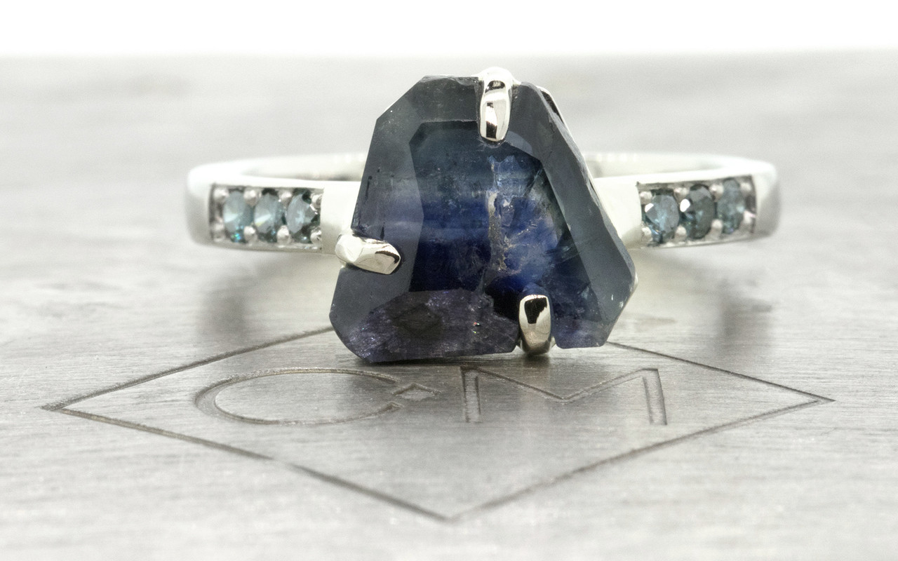 2.45 carat hand-cut deep blue signature inlaid prong set  sapphire and blue diamond ring in 14k white gold. With six 1.7mm brilliant blue diamonds bead-set in 1/2 round 14k recycled white gold band. Part of our Refined Rough Collection. Front view on metal background with Chinchar/Maloney logo