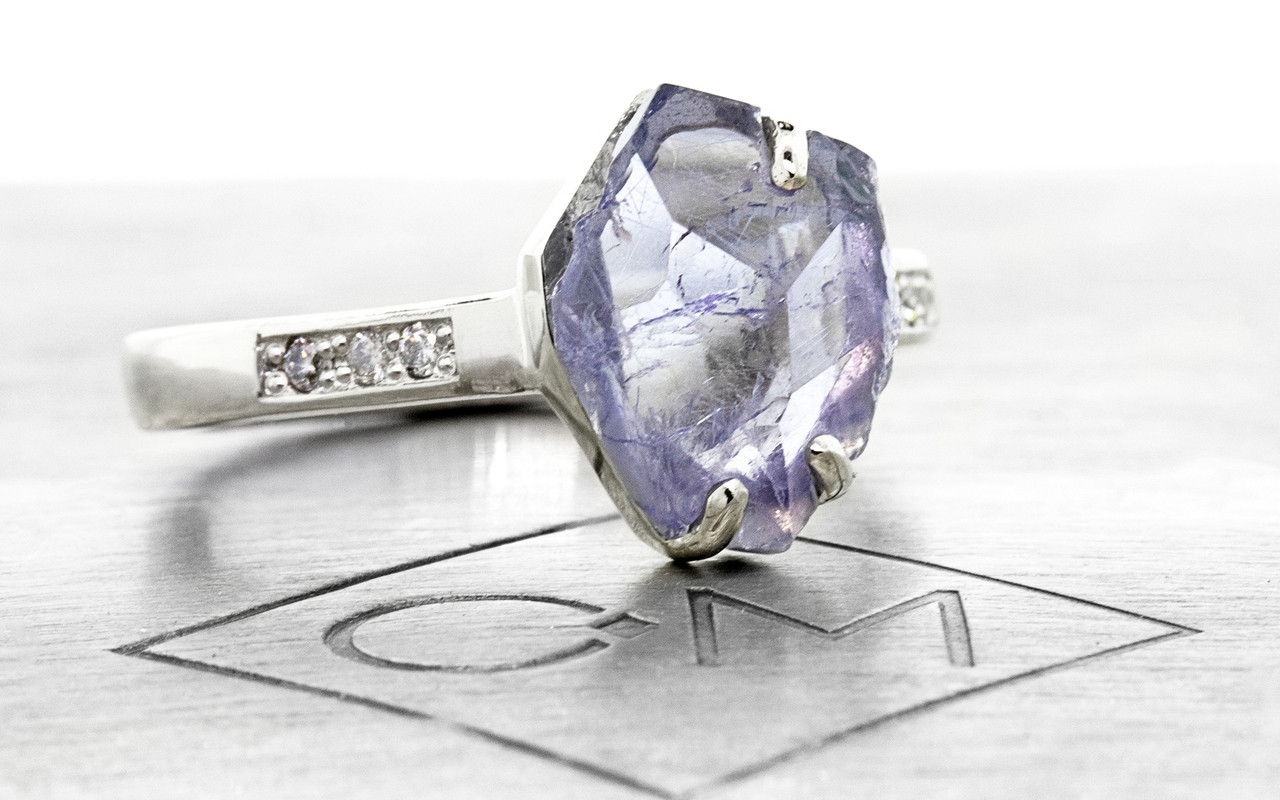 1.96 carat partially hand-cut and polished tanzanite inlaid prong set ring, with six 1.2mm brilliant gray diamonds bead set into 14k recycled white 2.5mm wide gold band. Part of our Refined Rough Collection. 3/4 view on metal background with Chinchar/Maloney logo