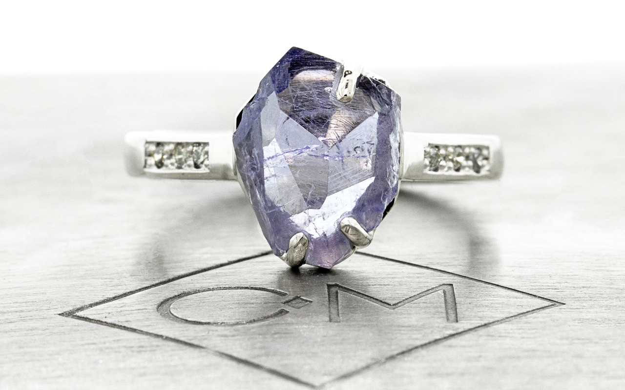 1.96 carat partially hand-cut and polished tanzanite inlaid prong set ring, with six 1.2mm brilliant gray diamonds bead set into 14k recycled white 2.5mm wide gold band. Part of our Refined Rough Collection. Front view on metal background with Chinchar/Maloney logo.