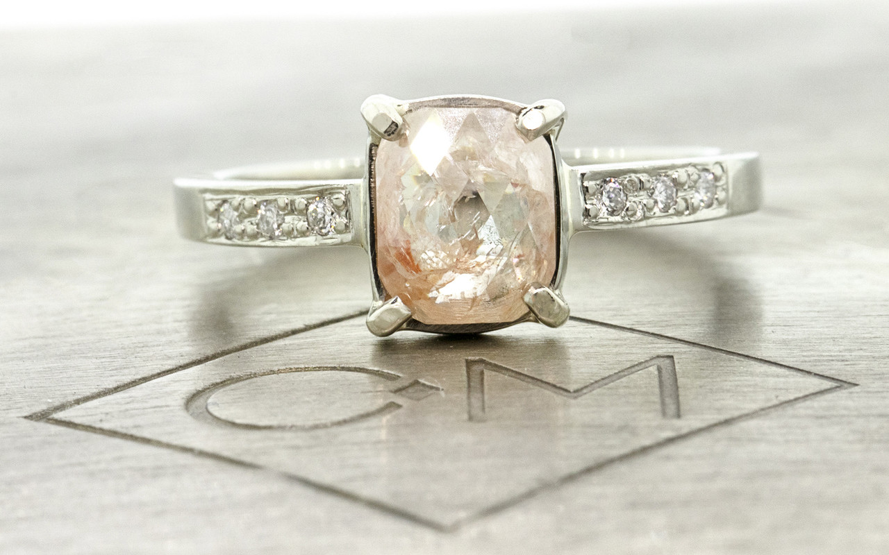 .82 carat sparkly light peach cushion rose cut prong set diamond ring, with six 1.2mm brilliant white diamonds bead set into 14k recycled white 2mm wide gold band. Front view on metal background with Chinchar/Maloney logo