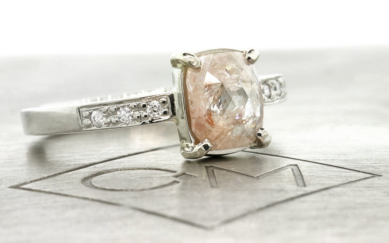 .82 carat sparkly light peach cushion rose cut prong set diamond ring, with six 1.2mm brilliant white diamonds bead set into 14k recycled white 2mm wide gold band. 3/4 view on metal background with Chinchar/Maloney logo
