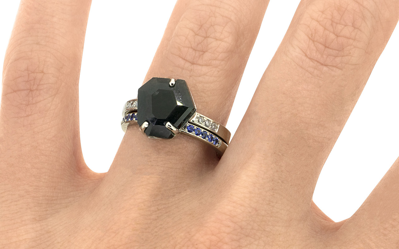 3.88 carat one-of-a-kind, partially hand-cut and polished prong set in our original design have been inlaid into grooves carved into dark blue sapphire ring. With six 1.2mm brilliant gray diamonds bead set into 14k recycled white gold 2mm band. With Wedding Band with sixteen 1.2mm brilliant blue sapphires bead set in a row in 14k recycled white gold 2mm band on a hand.  Part of our Refined Rough Collection.