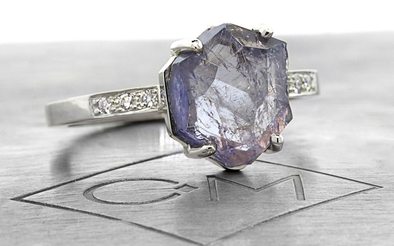 one-of-a-kind, partially hand-cut and polished, 1.96 carat tanzanite ring. prongs in our original design have been inlaid into grooves carved into the gem for a secure and smooth setting. Six 1.2mm brilliant gray diamonds have been bead-set into the band on each side of the tanzanite. 14k recycled white 2mm wide flat gold band.  3/4 view on metal background with Chinchar/Maloney logo