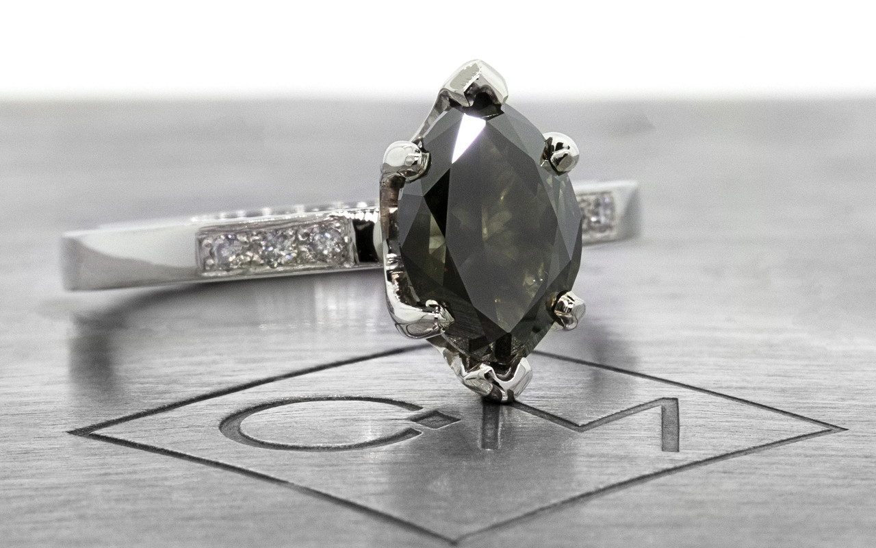 One of a kind, this natural, translucent, black diamond weighs 1.53 carats. marquise, faceted cut prong set diamond. Set into 14k recycled white gold 2mm flat band with six 1.2mm brilliant gray diamonds bead set into band. 3/4 view on metal background with Chinchar/Maloney logo