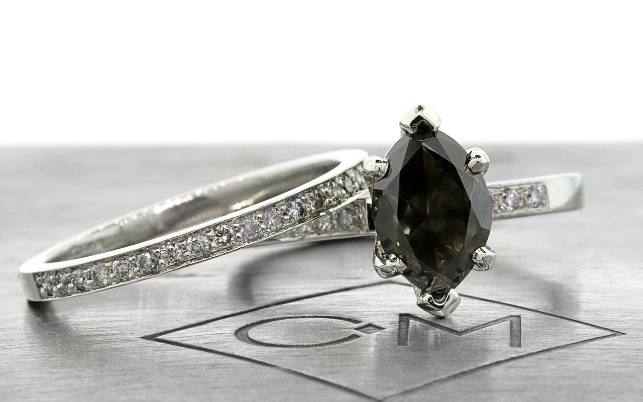 One of a kind, this natural, translucent, black diamond weighs 1.53 carats. marquise, faceted cut prong set diamond. Set into 14k recycled white gold 2mm flat band with six 1.2mm brilliant gray diamonds bead set into band. With Wedding Band with sixteen 1.2mm brilliant gray diamonds bead set into 14k recycled white gold 2mm 1/2 round band. Front view on metal background with Chinchar/Maloney logo