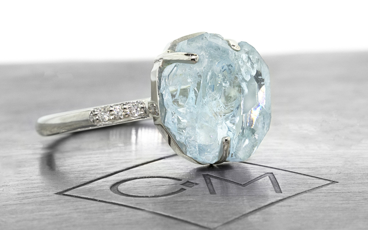one-of-a-kind, partially hand-cut and polished, 4.04 carat sparkly and translucent, bright blue aquamarine. Prong set. Six 1.2mm brilliant white diamonds have been bead-set into the 14k recycled white gold 2mm 1/2 round band. Part of our Refined Rough Collection. 3/4 view on metal background with Chinchar/Maloney logo