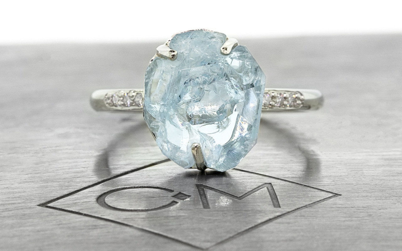 one-of-a-kind, partially hand-cut and polished, 4.04 carat sparkly and translucent, bright blue aquamarine. Prong set. Six 1.2mm brilliant white diamonds have been bead-set into the 14k recycled white gold 2mm 1/2 round band. Part of our Refined Rough Collection. Front view on metal background with Chinchar/Maloney logo