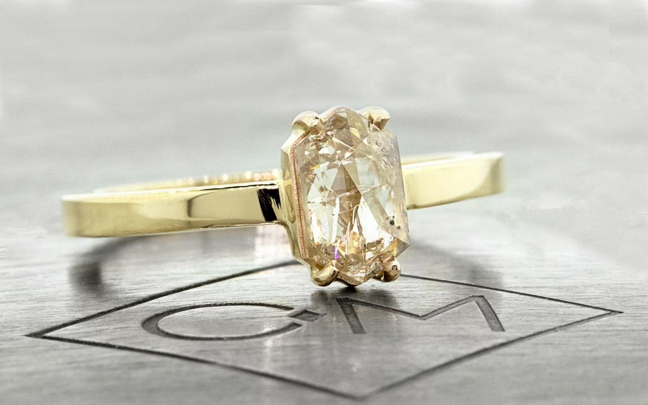 One of a kind, this .67ct diamond has a sparkling and translucent, light champagne color. hexagonal, fancy, rose cut diamond that measures 8mm x 5.25mm. 14k recycled yellow gold with a band that measures 2mm wide. 3/4 view on metal background with Chinchar/Maloney logo