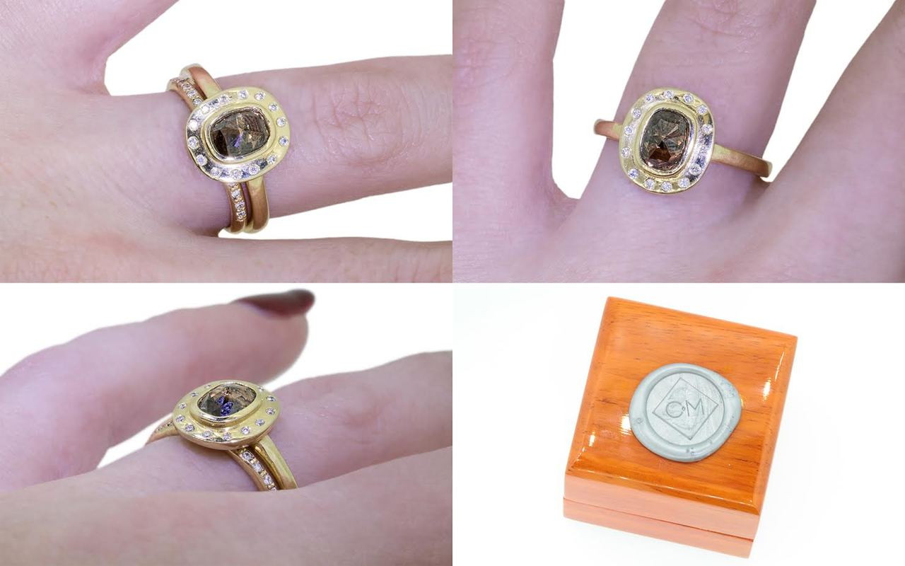 .98 carat rose cut dark cognac cast in place diamond with fourteen brilliant white diamond halo ring set in 14k yellow gold 1/2 round band. With Wedding Band with 16 brilliant white diamonds set in 14k yellow gold 1/2 round band on a hand with wooden box stamped with wax seal Chinchar/Maloney logo