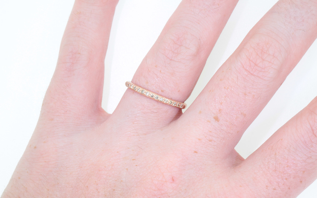 14k yellow gold wedding band with 16 brilliant champagne pave diamonds half way around band. Modeled on hand