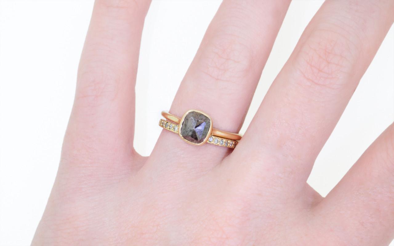 14k yellow gold wedding band with 16 brilliant gray diamonds half way around band modeled on hand with gray diamond ring.