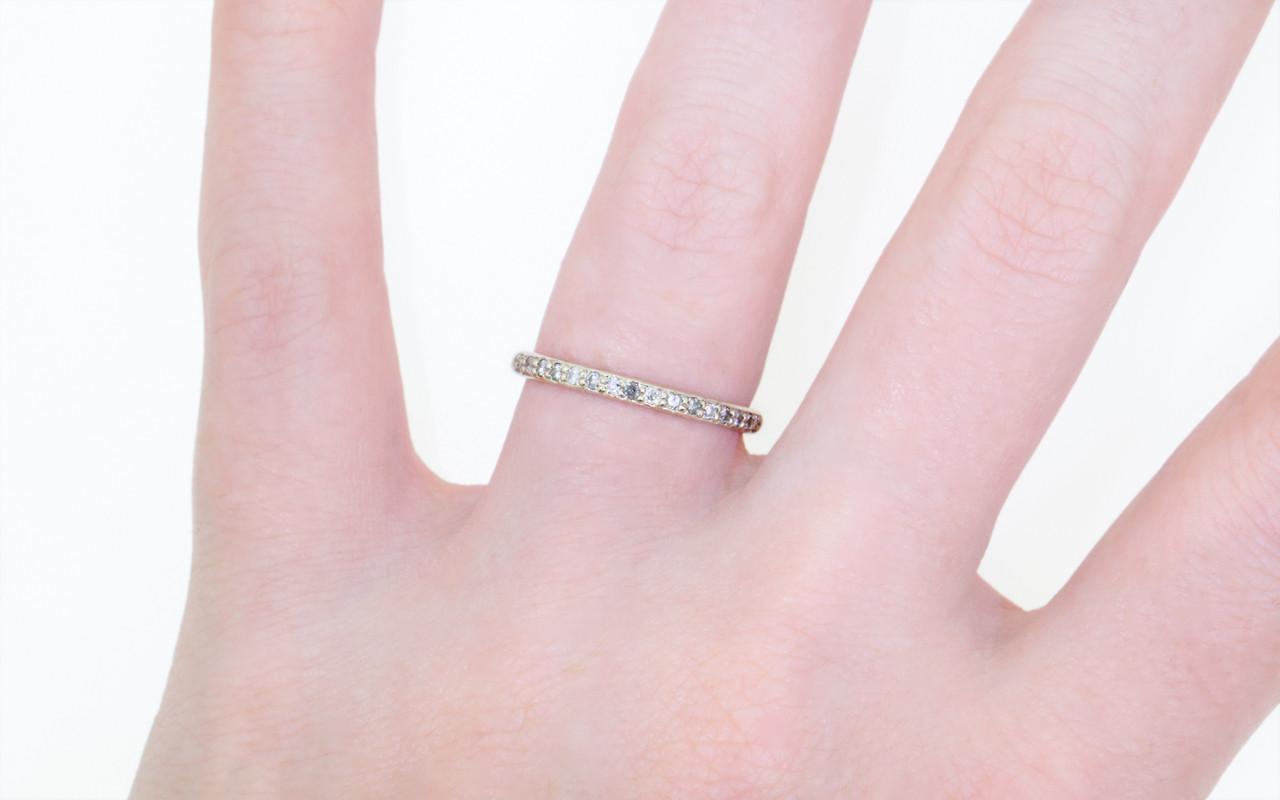 14k white gold wedding band with 16 brilliant gray pave diamonds half way around band modeled on hand