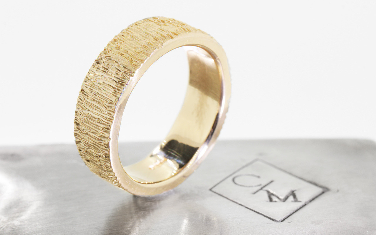 14k yellow gold hand carved textured mens wedding band on metal background with Chinchar/Maloney logo.
