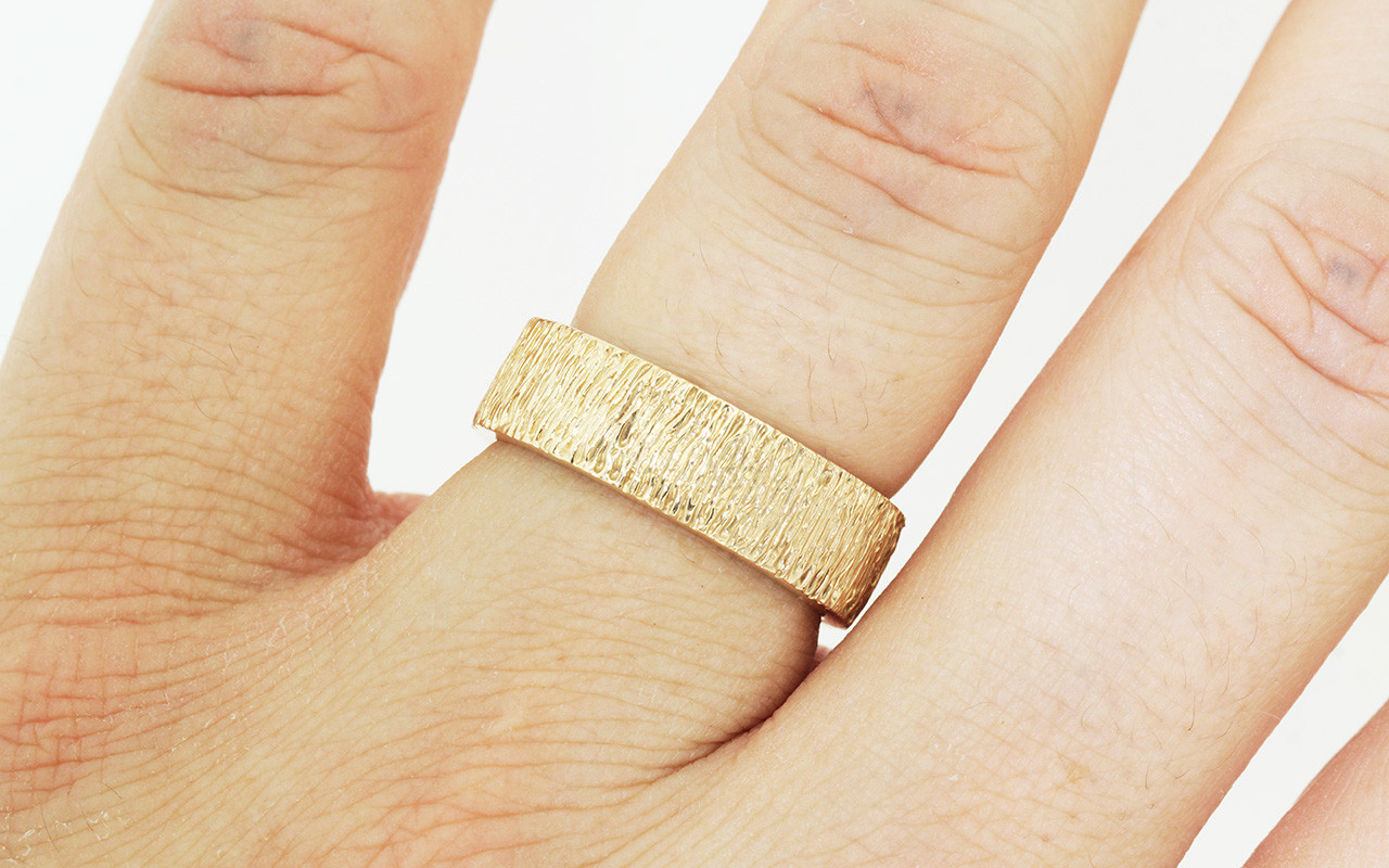 14k yellow gold hand carved textured mens wedding band. Modeled on hand