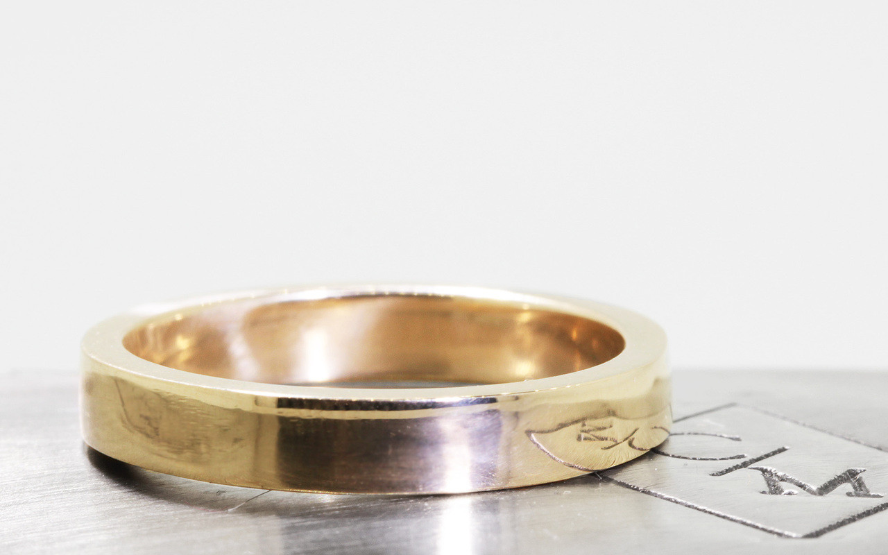 14k yellow gold flat men's wedding band on metal background with Chinchar/Maloney logo