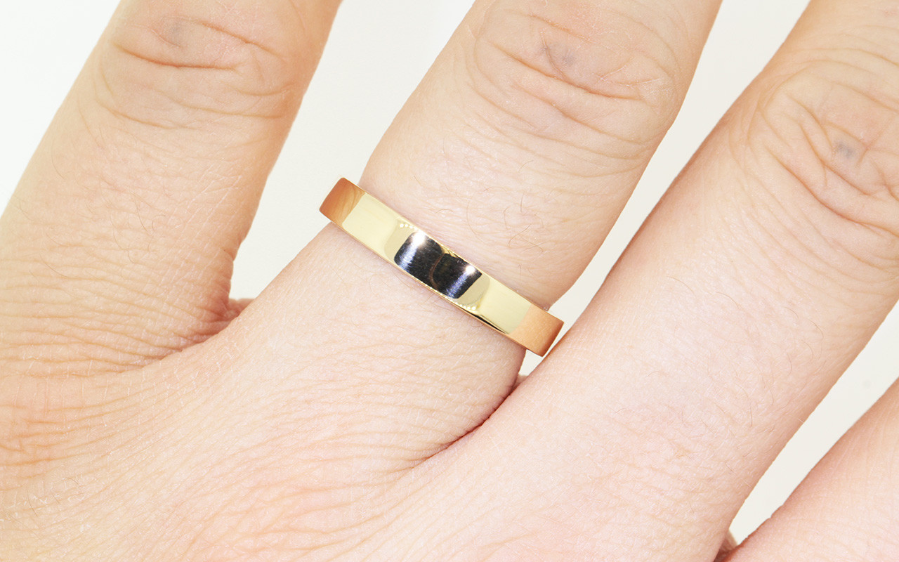 14k yellow gold flat mens band modeled on hand