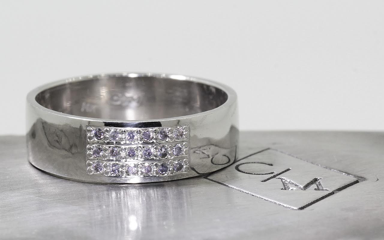6.5mm wide flat wedding band in 14k white gold with a block of pave set gray diamonds on the top.  Front view metal background with Chinchar/Maloney logo.