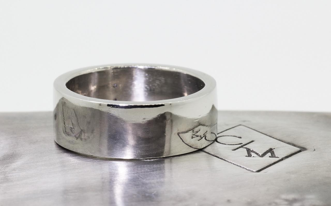 8mm wide flat wedding band in 14k white gold.  Polished finish.  Metal background with Chinchar/Maloney logo.